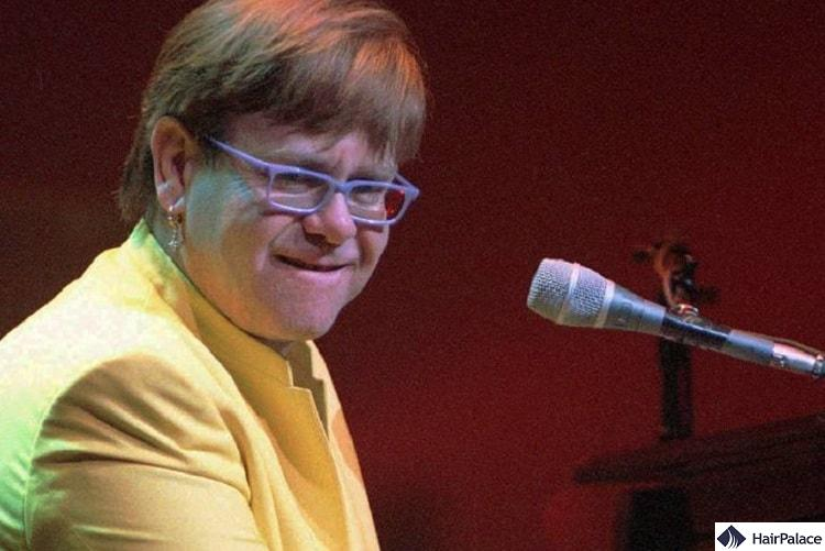 Elton John with a wig peforming in 1997.